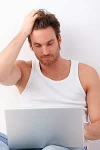 Athletic young man using laptop, browsing internet.